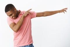 Erfüllter junger Kerl des glücklichen und charismatischen frohen Afroamerikaners, der den Klecks zieht Hände, unten schauend nach stockbild
