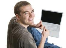 Erfüllter junger Mann, der einen Laptop verwendet Lizenzfreie Stockfotos