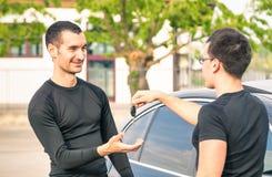 Erfüllter Käufermann, der Autoschlüssel nach zweite Handverkauf empfängt Stockfotos