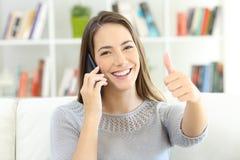 Erfüllter Kunde, der am Telefon spricht und Sie betrachtet stockfoto