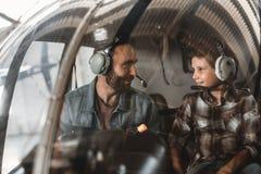 Erfüllter Mann, der mit Kind im Hubschrauber sich verständigt lizenzfreies stockfoto