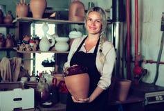Erfüllter weiblicher Handwerker, der Keramik in der Werkstatt hat stockfotos