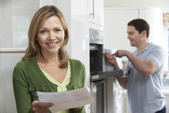 Erfüllter weiblicher Kunde mit Oven Repair Bill Stockbild