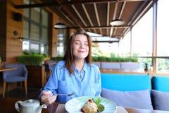 Erfülltes Mädchen, das Nachtisch am Restaurant isst lizenzfreies stockfoto
