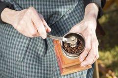 Erfahrene Arbeiter, die Kaffee auf einer Weinlesekaffeemühle reiben stockfoto