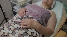 Erfahrene Arbeiter einer älteren Frau, die auf der Couch im Cosmetology liegt stock video