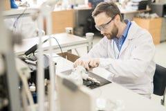 Erfahrene Arbeitskraft, die Messgerät auseinander nimmt stockfotos