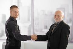 Erfahrene Führungskraft, die Hände mit jungem Angestelltem rüttelt Stockfotos
