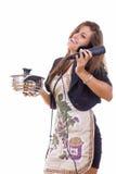 Erfahrene Geschäftsfrau, die am Telefon kocht und spricht Stockfotos