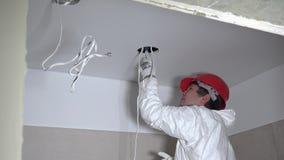 Erfahrene männliche Arbeitskraft, die Fasergipsplattendeckenlöcher für Beleuchtungsanlage macht stock video