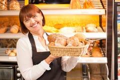Erfahrene Verkäuferin stellt gebackene Produkte dar Stockfoto