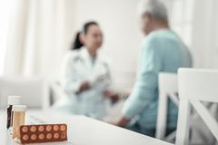 Erfahrene zuverlässige Krankenschwester, die mit ihrem Patienten sitzt und spricht stockbilder