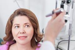 Erfahrener Augenarzt überprüft Augen des Patienten Lizenzfreie Stockfotografie