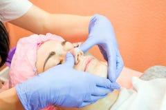 Erfahrener Cosmetologist wendet eine Maske der Emulsion an lizenzfreies stockbild