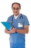 Erfahrener Doktor, der an der Kamera lächelt lizenzfreies stockfoto
