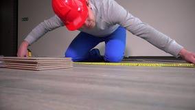 Erfahrener Erbauer mit rotem Schutzhelmlage-Laminatsbodenbelag an der Baustelle stock footage