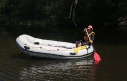 Erfahrener Führer schwimmt auf einem weißen Floss allein auf dem Fluss stockfotografie