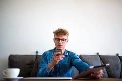 Erfahrener Freiberufler des stilvollen Hippie-Kerls, der online über Smartphone nach Telearbeit plaudert lizenzfreie stockfotografie