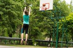 Erfahrener junger Basketball-Spieler, der ein Ziel schießt Stockfotos