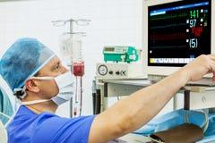 Erfahrener männlicher Anaesthesiologist am Monitor lizenzfreie stockfotografie