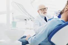 Erfahrener männlicher Zahnarzt, der Patienten kuriert lizenzfreies stockbild