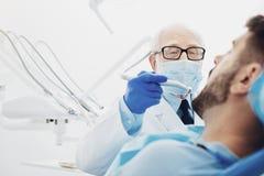 Erfahrener männlicher Zahnarzt, der Zahn ersetzt stockfotos