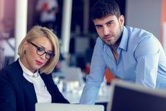 Erfahrener professioneller blonder Frau CEO, der jungem männlichem Angestelltem erklärt, fordert und Strategie Lizenzfreie Stockbilder