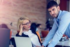 Erfahrener professioneller blonder Frau CEO, der jungem männlichem Angestelltem erklärt, fordert und Strategie Stockfotos