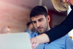 Erfahrener professioneller blonder Frau CEO, der jungem männlichem Angestelltem erklärt, fordert und Strategie Lizenzfreie Stockfotografie