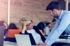 Erfahrener professioneller blonder Frau CEO, der jungem männlichem Angestelltem erklärt, fordert und Strategie Stockbilder