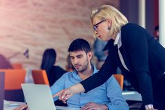Erfahrener professioneller blonder Frau CEO, der jungem männlichem Angestelltem erklärt, fordert und Strategie Lizenzfreies Stockbild