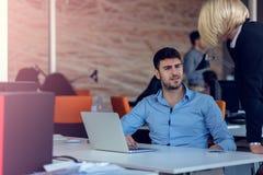 Erfahrener professioneller blonder Frau CEO, der jungem männlichem Angestelltem erklärt, fordert und Strategie Lizenzfreie Stockfotos