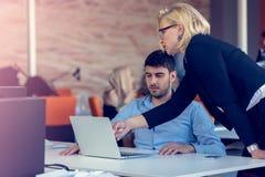 Erfahrener professioneller blonder Frau CEO, der jungem männlichem Angestelltem erklärt, fordert und Strategie Stockbild