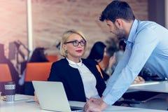 Erfahrener professioneller blonder Frau CEO, der jungem männlichem Angestelltem erklärt, fordert und Strategie Stockfotografie