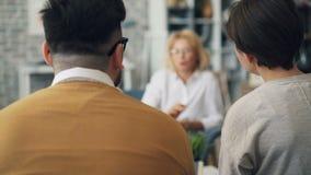 Erfahrener Psychologe, der Rat zu den jungen Paaren kämpfen an der Sitzung gibt stock footage