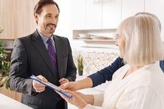 Erfahrener Rechtsanwalt, der Beratung zu den älteren Paaren über großen Kauf gibt stockbild
