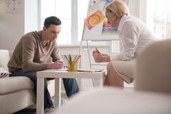 Erfahrener reifer Psychologe, der Kunsttherapie vorstellt Stockbild