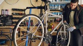 Erfahrener Schlosser wird auf die Reparatur der Fahrradfelge konzentriert, die es mit Berufsschlüssel beim Arbeiten in kleinem re stock video footage