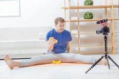 Erfahrener Trainer, der mit einem Handgewicht sitzt und die Kamera betrachtet Lizenzfreie Stockfotos