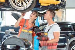 Erfahrener weiblicher Automechaniker mit ihrem Kollegen Lizenzfreie Stockbilder