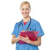 Erfahrener weiblicher Doktor, der an der Kamera lächelt Lizenzfreies Stockbild
