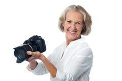 Erfahrener weiblicher Fotograf mit Kamera Lizenzfreie Stockfotos