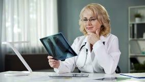 Erfahrener weiblicher Radiologe, der Röntgenstrahlbild, qualifizierte Diagnosen studiert stockbild