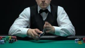 Erfahrenes Croupier, das Karten schlurft und As in die Kamera, spielend zeigt stock video