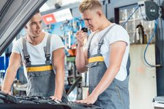 Erfaren auto mekaniker som kontrollerar delarna av en bil royaltyfri fotografi