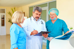 Erfaren doktor och medicinsk personal som konsulterar om vård- rekord i sjukhus Royaltyfri Foto