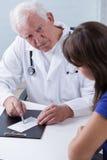 Erfaren läkare som ger receptet Arkivfoton