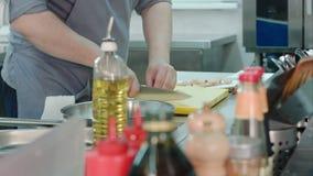 Erfaren manlig kock` s räcker att hugga av vitlök på ett plast- bräde lager videofilmer
