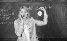 Erfaren utbildarestartkurs Hon att bry sig om disciplin Vilken tid ?r det Ringklocka f?r kvinnal?rareh?ll flicka royaltyfri bild