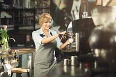 Erfaret baristadanandekaffe i yrkesmässig kaffemaskin royaltyfri foto